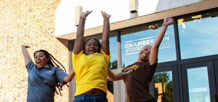Three Rowan students jumping in front of the Chamberlain Student Center