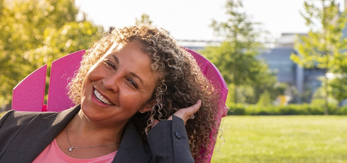 Woman sitting in pink lawn chair laughing while the sun shines down
