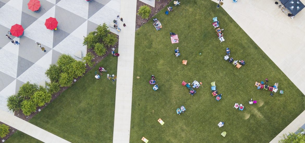 Aerial view of multiple people sitting in lawn chairs in a grassy town square