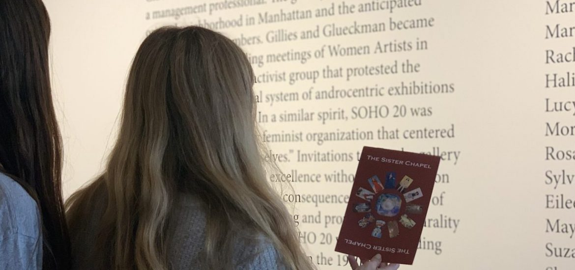 Two girls in the art gallery looking at The Sister Chapel Pamphlet