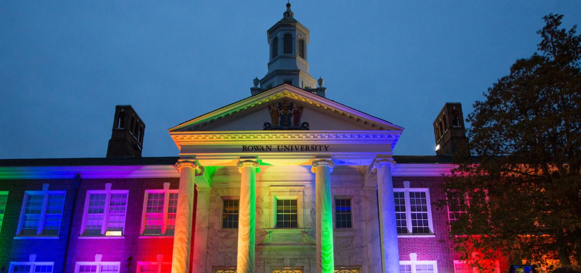 The front of Bunce Hall being lit up at night with rainbow colored lights