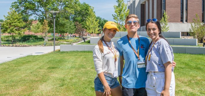 A group photo of three freshmen outside Wilson Hall