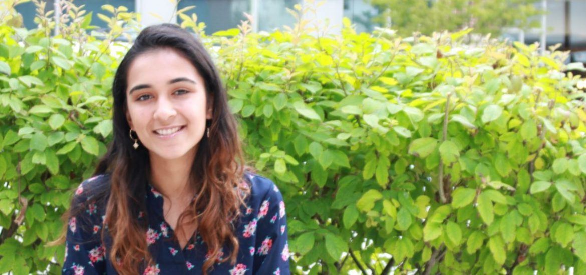 Molecular and cellular biology major Amaal Khan sits outside on a bench