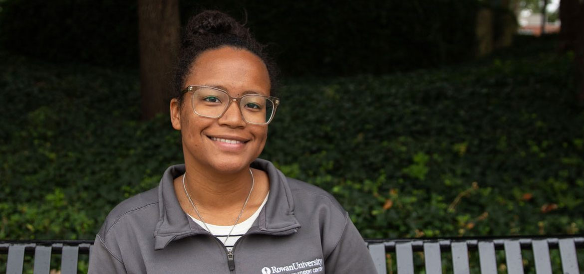 Autumn Vilches-Cruz, junior Psychology major, sitting on a bench outside on Rowan's campus