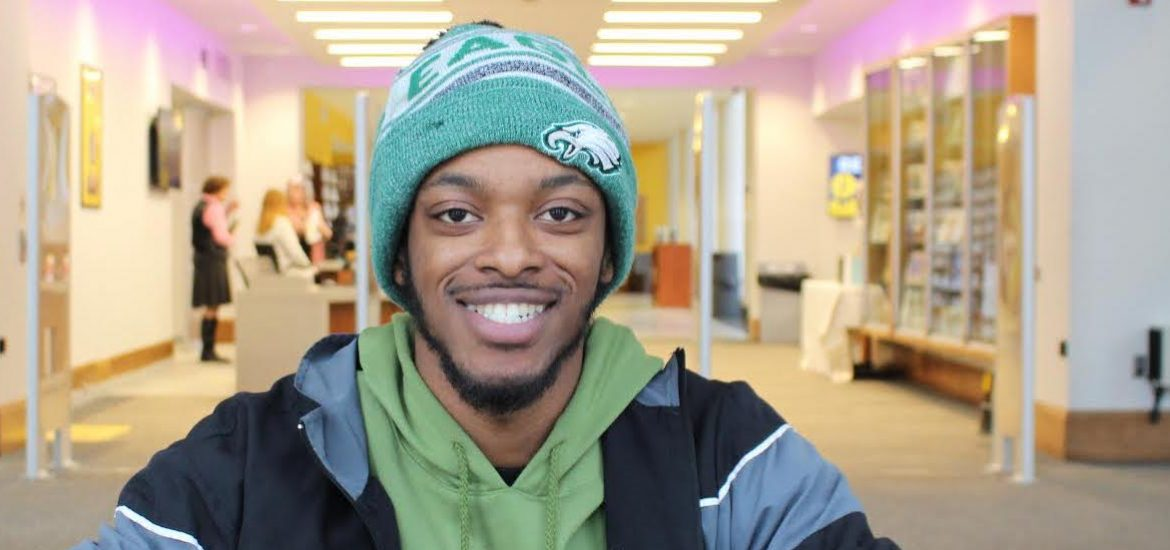 Jamal sitting in the library with a green beanie on.