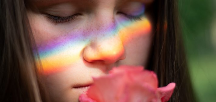A close up photo of a girl holding a rose to her face.