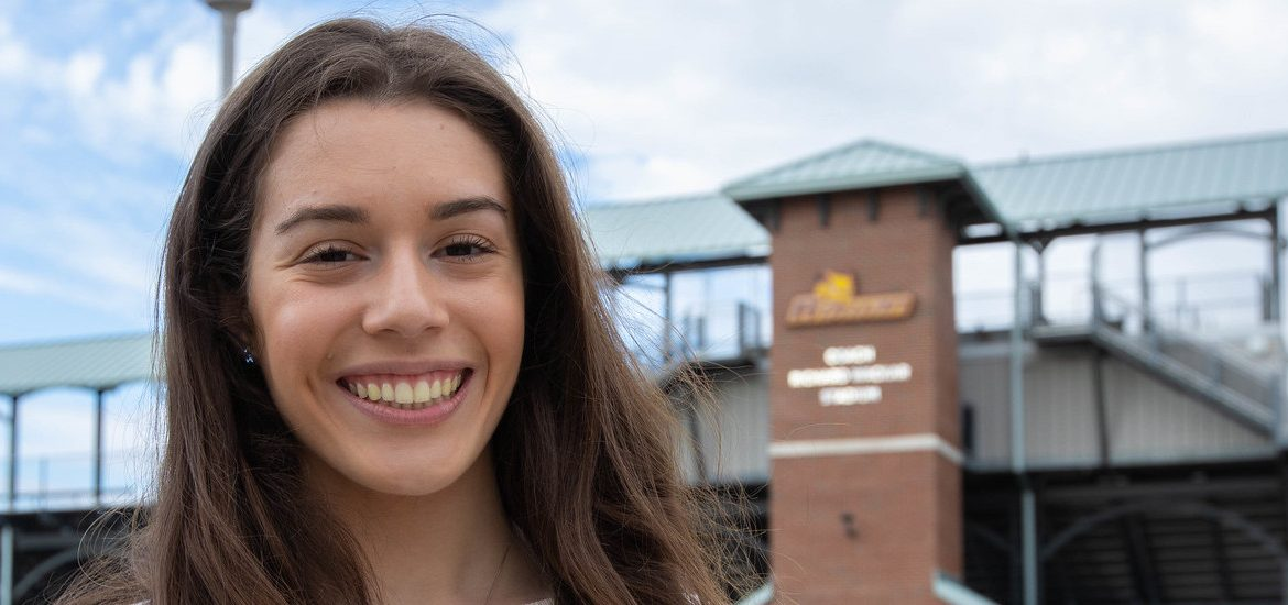 Kayla smiles and stands in front of Wackar Stadium