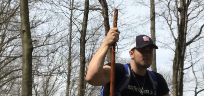 Eddie crouches in the woods, holding a walking stick.