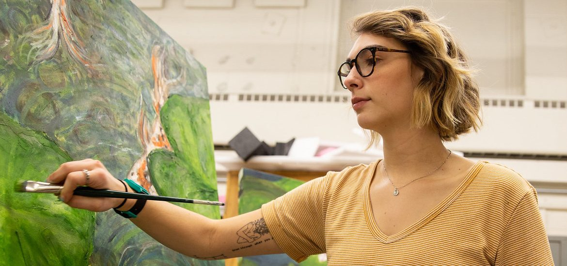 Jessica wears a yellow shirt while holding a paintbrush to her canvas, a nature painting of koi fish.