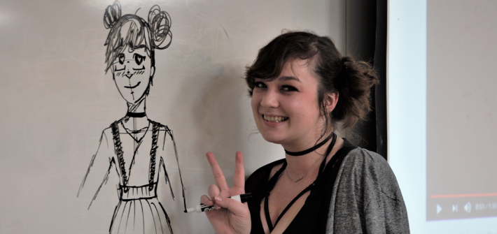 An Anime Club member draws an anime figure on the whiteboard at a club meeting
