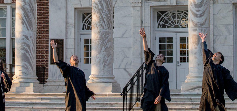 four grads toss their hat.