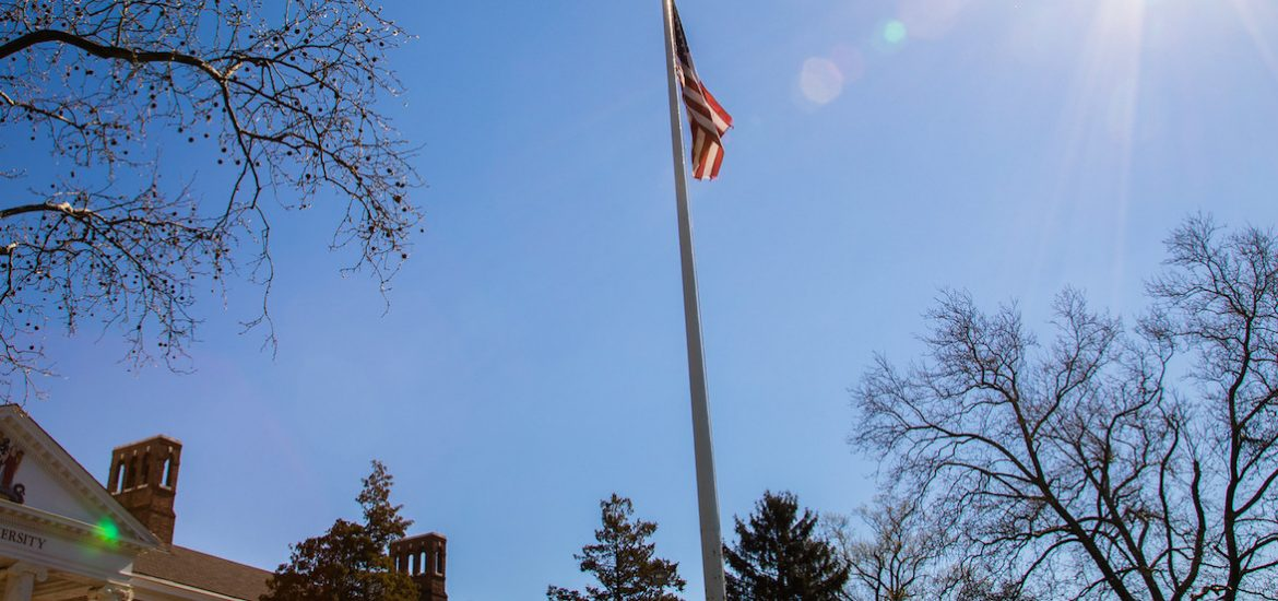 Bunce Hall, a flag, and the sun.