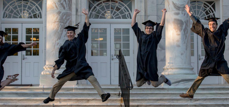 4 rowan grads jump in graduation attire.