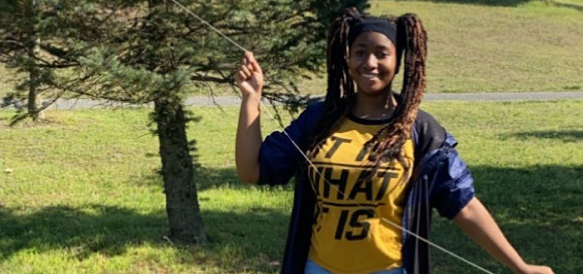 Photo of Maiyah outside in a yellow shirt and blue jacket