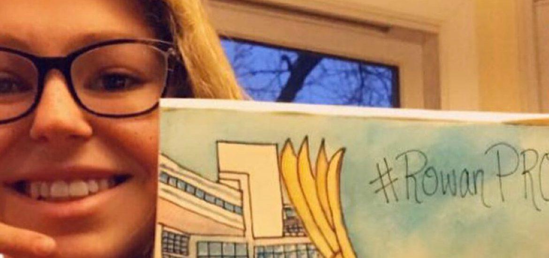 Selfie of Emma holding a drawing of Rowan.