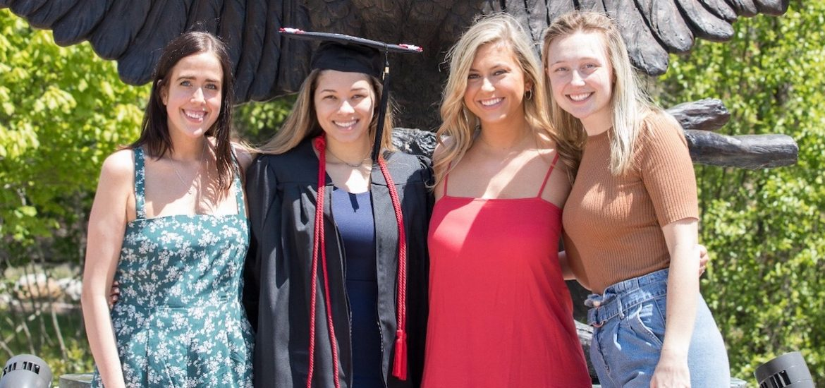 casey and three friends posing for a grad pic.