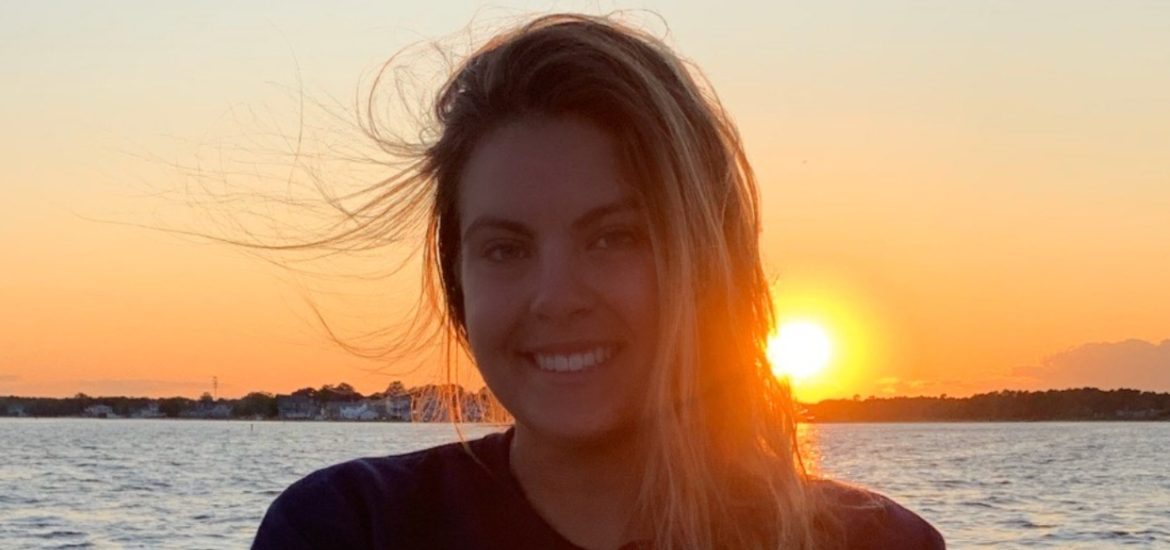 Taylor Melillo in front of a sunset on the water.