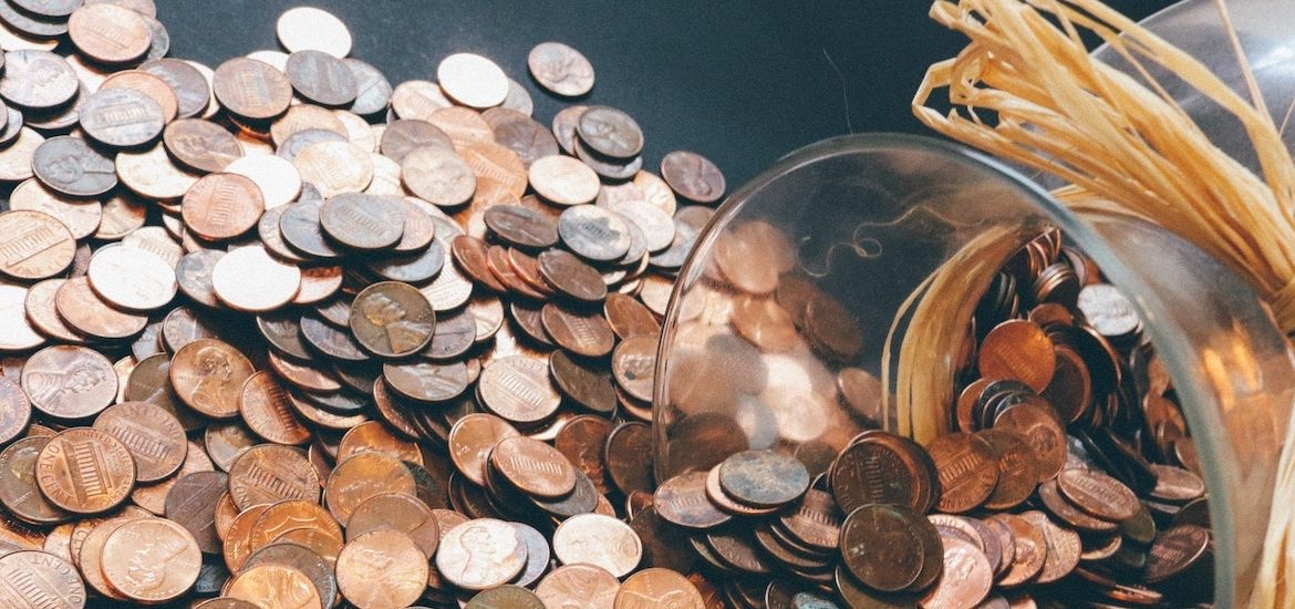 Stock image of pennies spilling out of a jar.