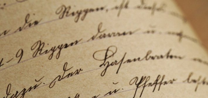 Stock image of black ink cursive on tepia colored paper.