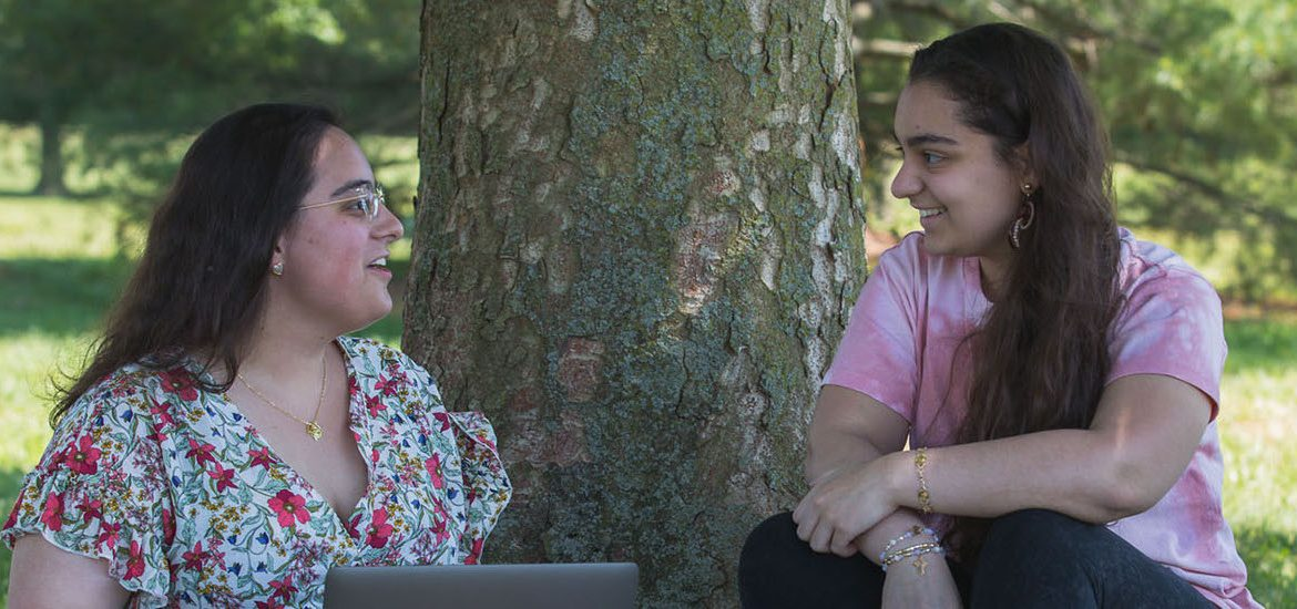 Marlo Rossi sits by a tree with her computer speaking to another student