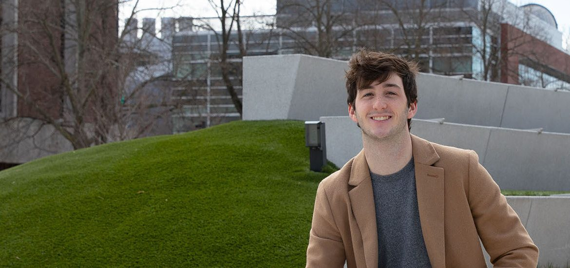 James Milward sits on the green next to Wilson Hall