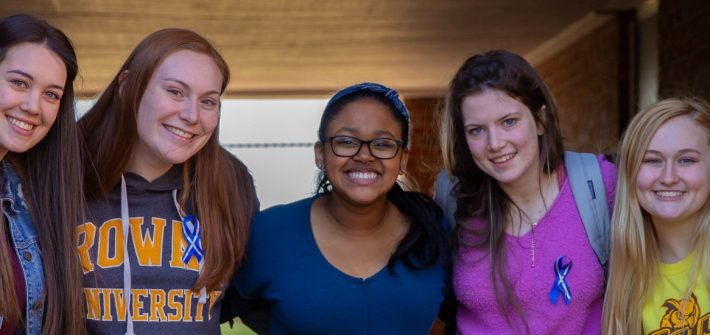 Five Rowan students posing and smiling outside on campus
