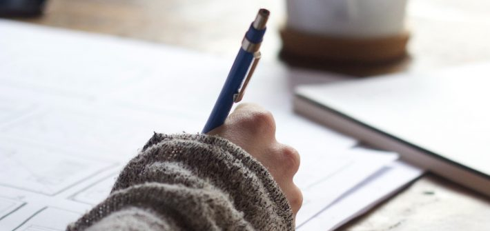 Stock image of a student writing in a notebook