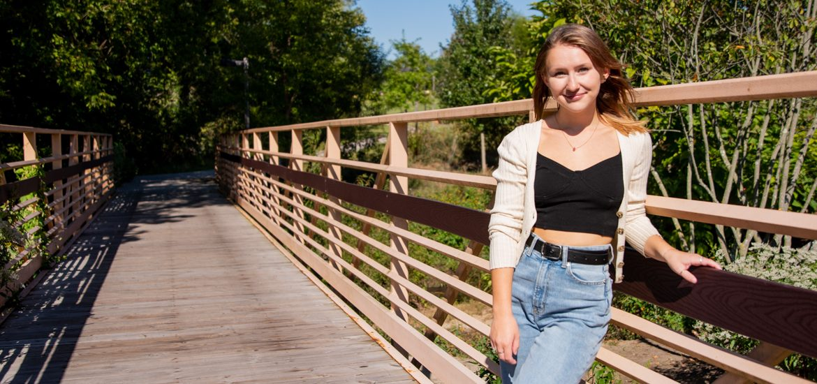 Angela stands on a bridge on campus.