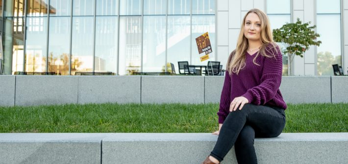 Exterior shot of Kailey Booth sitting on campus.