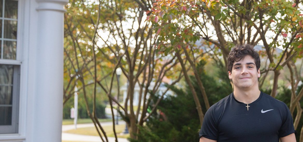 Noah Garcia smiles in front of trees with orange and green. A white building is close by on the left hand side.