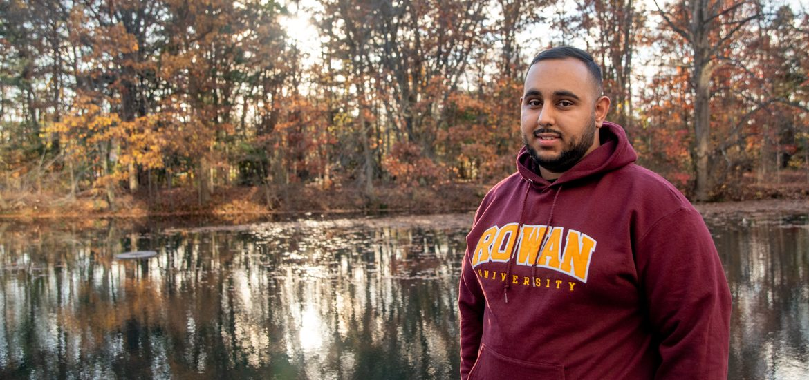 Muhammad standing in front of a pond.