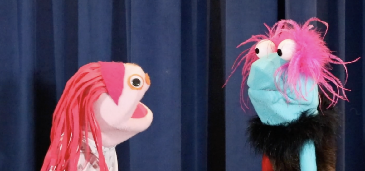 Two puppet in front of a blue backdrop.