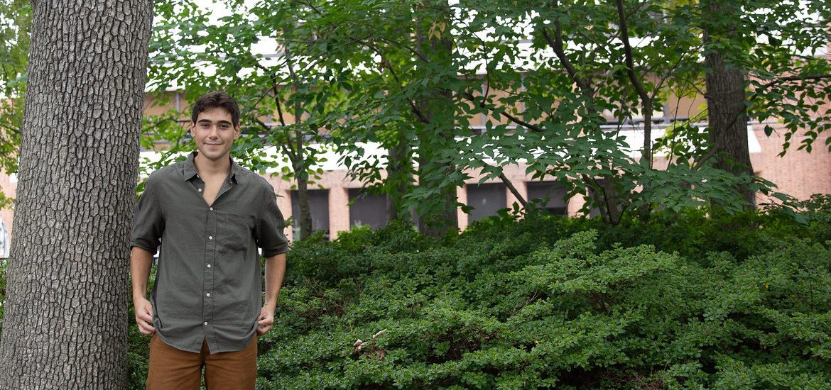 Marco stands in a wooded section of campus.