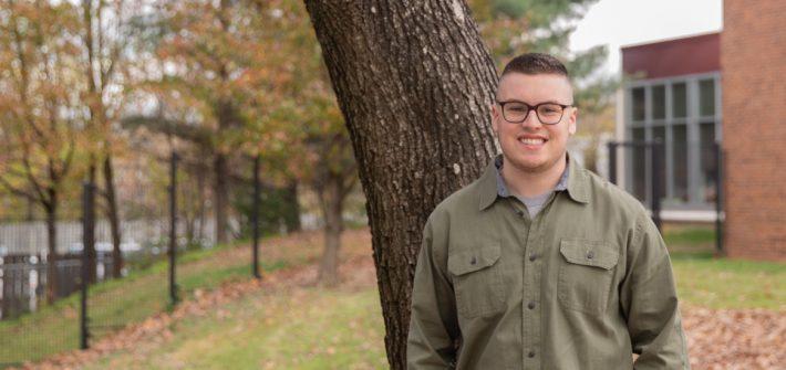 Brett poses next to a tree.