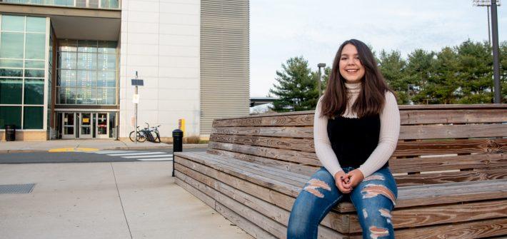 Helaina sitting on a bench outside.
