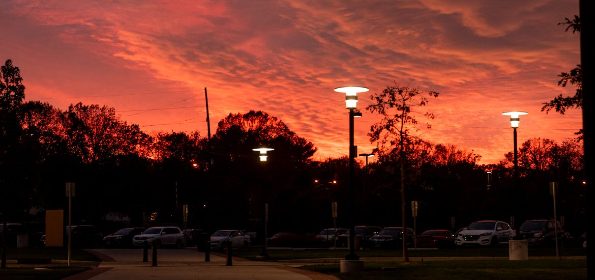 Sunset at Rowan with stark red sky against black silouette of buildings and trees.