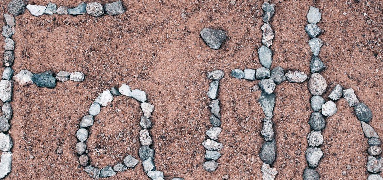 """The word """"faith"""" written using stones."""