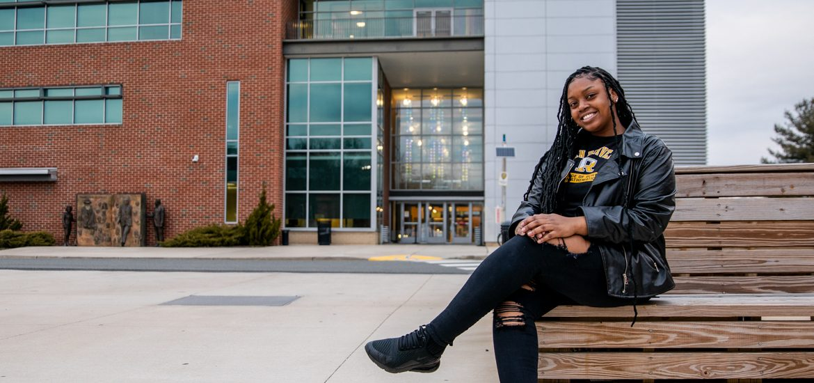Ylanda sits outside campus near Campbell Library.