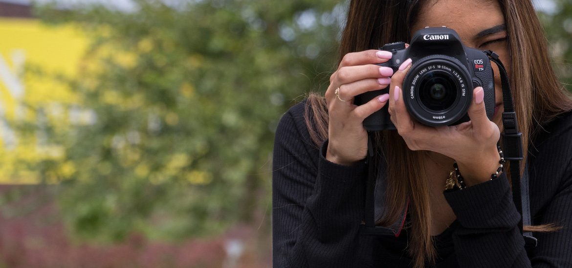 A Rowan student uses a DSLR camera to capture a moment.