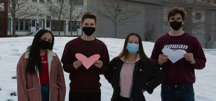 Rowan students hold hearts along Rowan Boulevard park area.