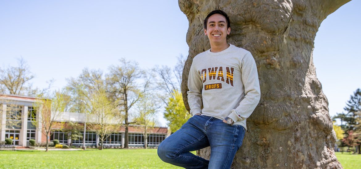 JT leans against a tree on Bunce green, wearing a Rowan sweater with hands in his pockets.