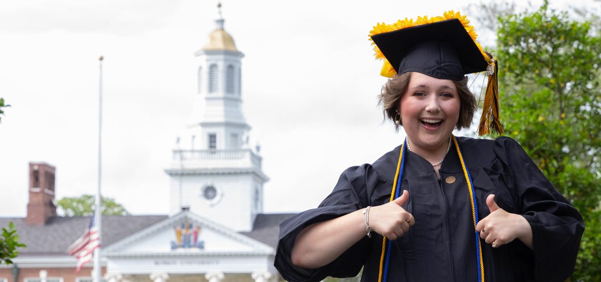 Student with cap and gown in front of Bunce.