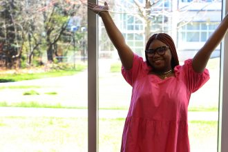 Dee poses ecstatically in a pink dress and glasses, with her hands up in the air.