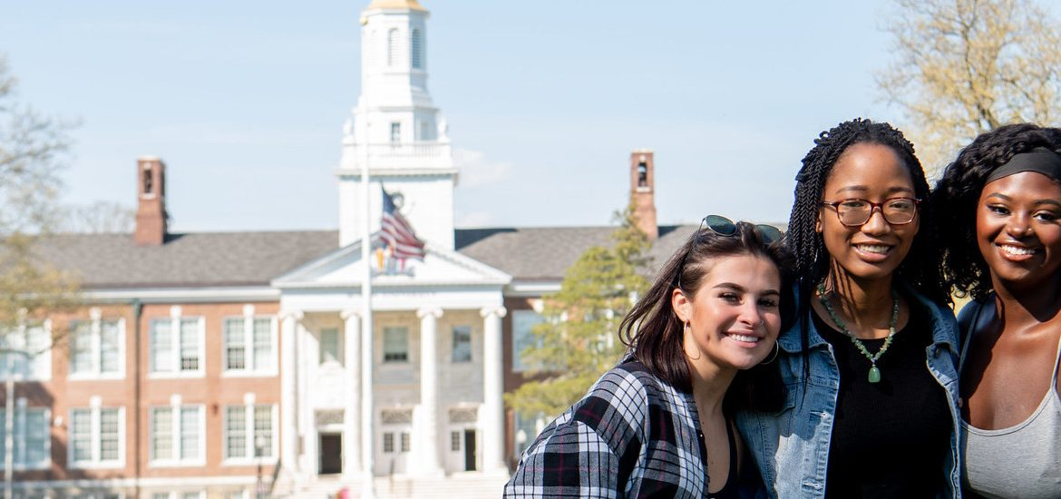 Three friends pose in front of Bunce Hall.