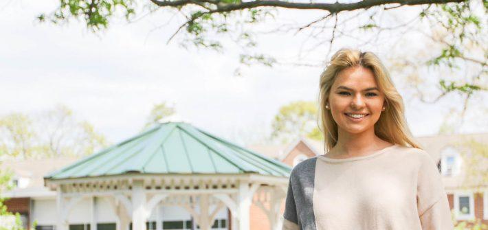 Caitlyn stands near a gazebo on campus.