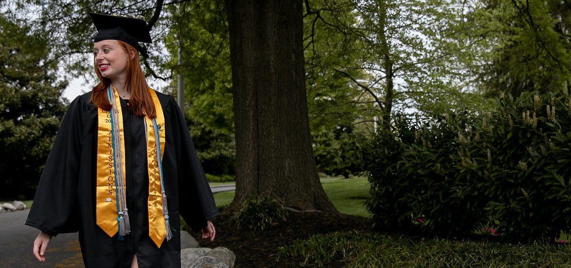 Ashley walks down Bunce Green in her cap and gown.