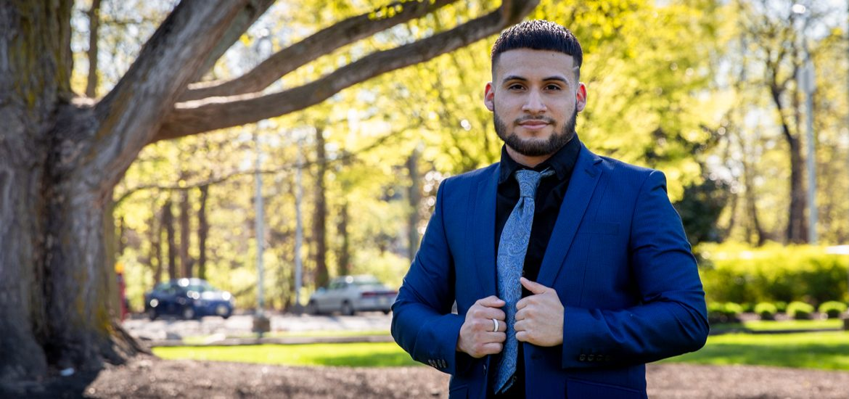 Anderson posing near a tree outside wearing a blue suit.
