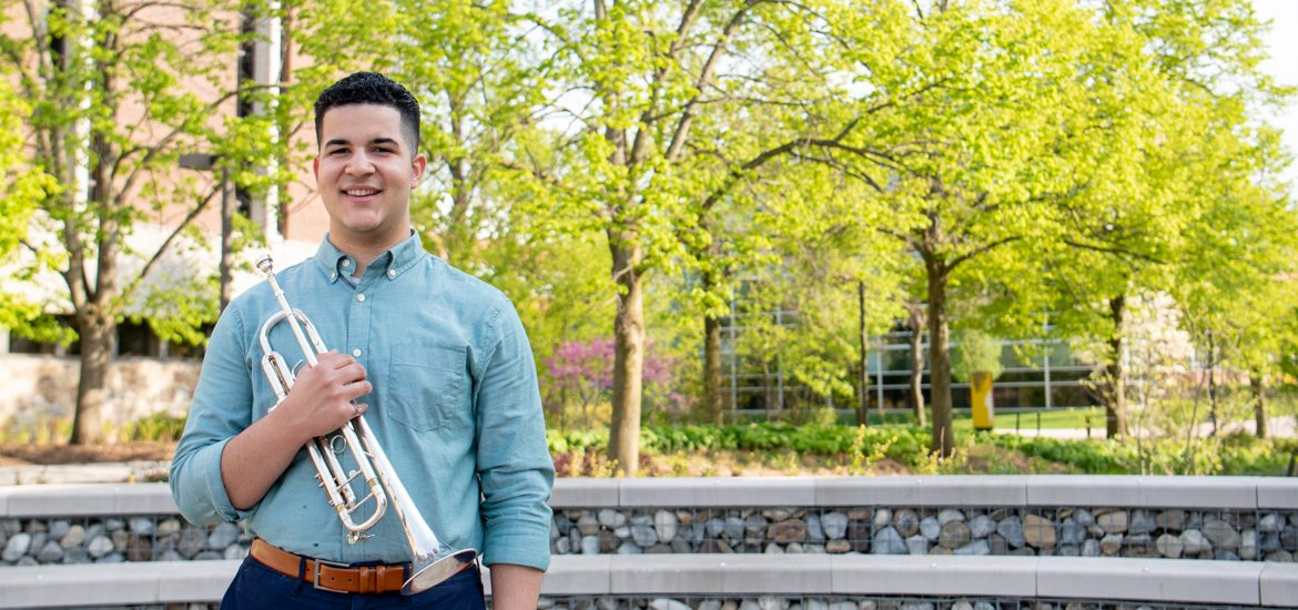 Luis stands with his trumpet outside on campus.