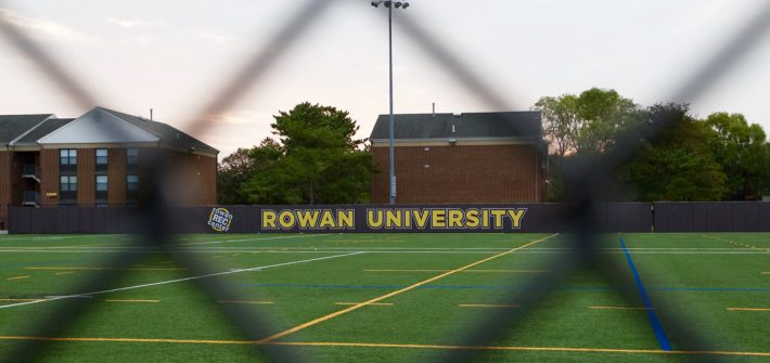 An athletic field as seen through a fence on campus.