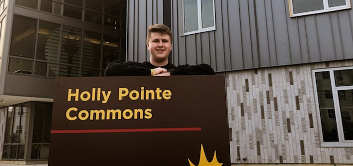 Mitch poses at the Holly Pointe Commons sign.